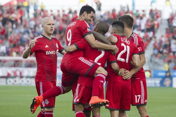 Toronto FC 's Justin Morrow (2) is mobbed by teammates after scoring his team's opening goal against Chicago Fire during first half MLS action in Toronto on Saturday August 23, 2014. THE CANADIAN PRESS/Chris Young ORG XMIT: CHY101